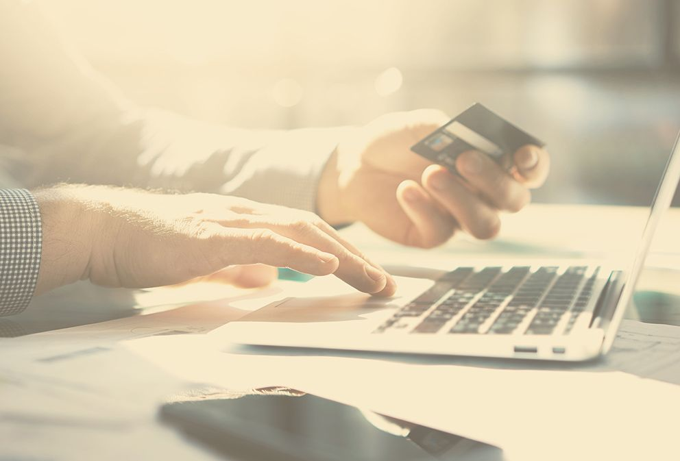 Trustee Services – man with credit card in hand using a computer